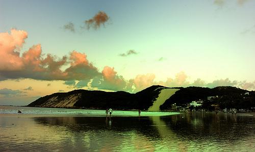 Fotografia panorâmica, colorida, em formato horizontal, da praia de Ponta Negra, com destaque, ao fundo, para o morro do careca, formação elevada com vegetação nativa com uma larga faixa de areia que se inicia na praia e finda no cume do morro. Algumas pessoas caminham perto das pequenas ondas que se quebram. Várias nuvens, em tom de rosa e vermelho, povoam o céu azul. Toda a paisagem é refletida na areia molhada da praia, saudando a manhã que chega. Fim da descrição.